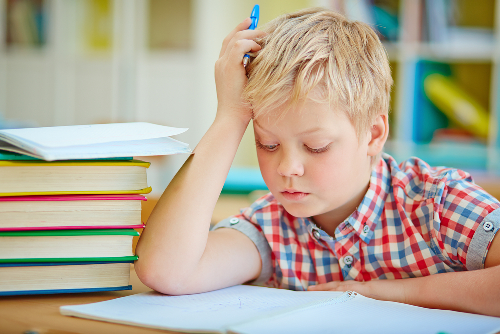 pensive-little-boy-looking-at-page-of-his-copybook-at-lesson