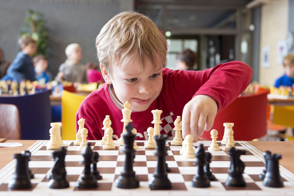 young-child-making-a-move-with-a-horse-during-a-chess-tournament-at-a-school-with-several-other