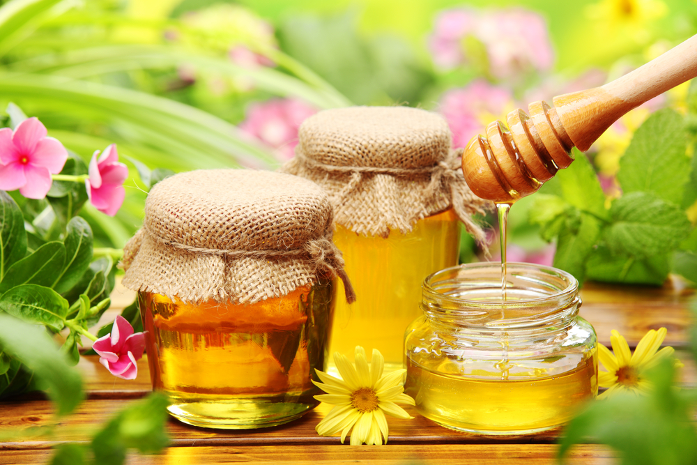 honey-in-glass-jars-with-flowers-background