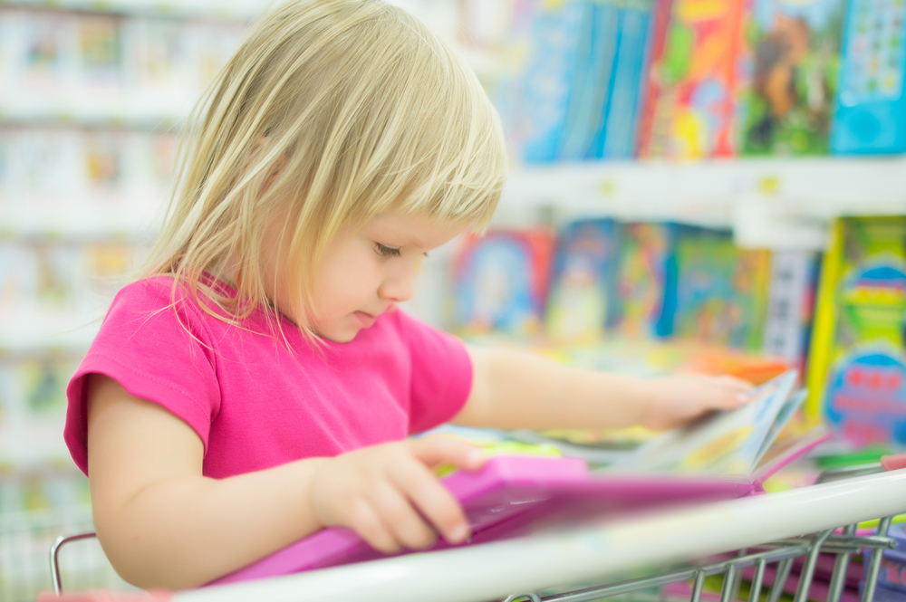 girl-reading-interactive-book-in-supermarket