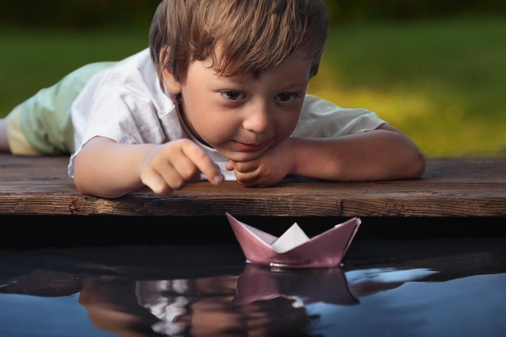 little-boy-releasing-paper-ship