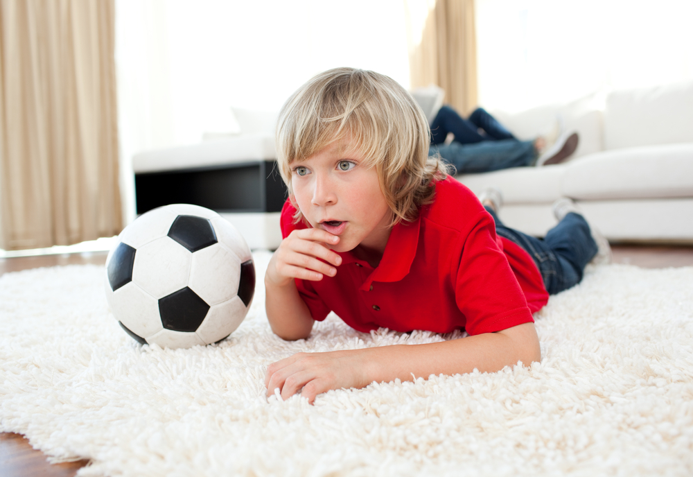 boy-watching-football-match-lying-on-the-floor-in-the-living-room