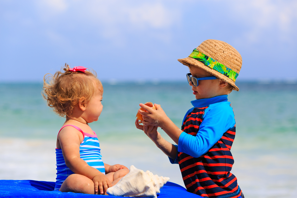 infant-girl-and-little-boy-playing-with-shells