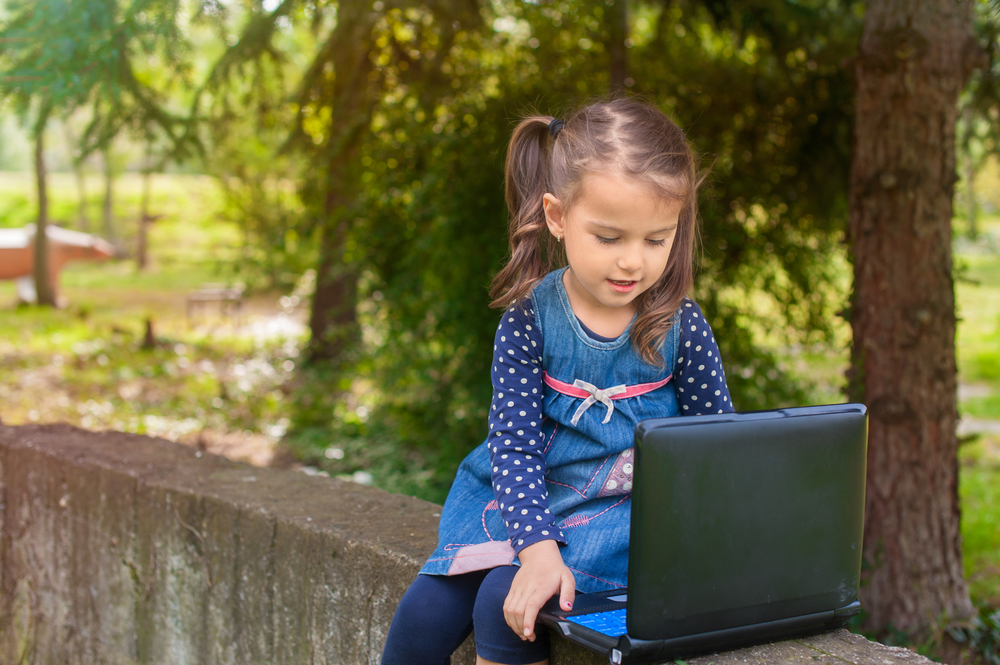 little-girl-learning-with-tablet-pc-in-the-park-outdoor