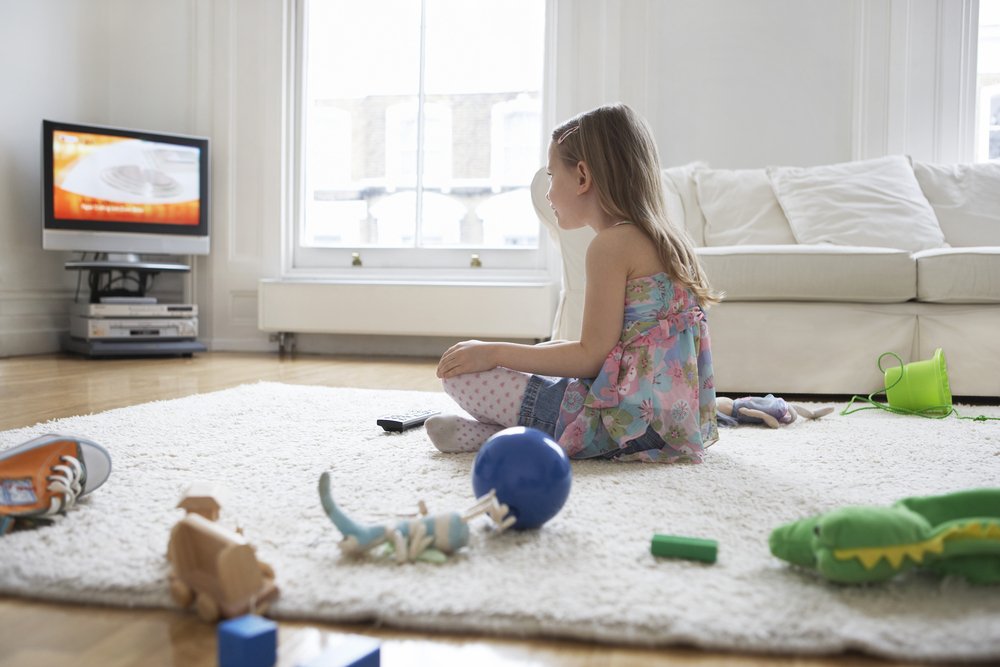 little-girl-watching-TV-with-her-toys-on-the-floor