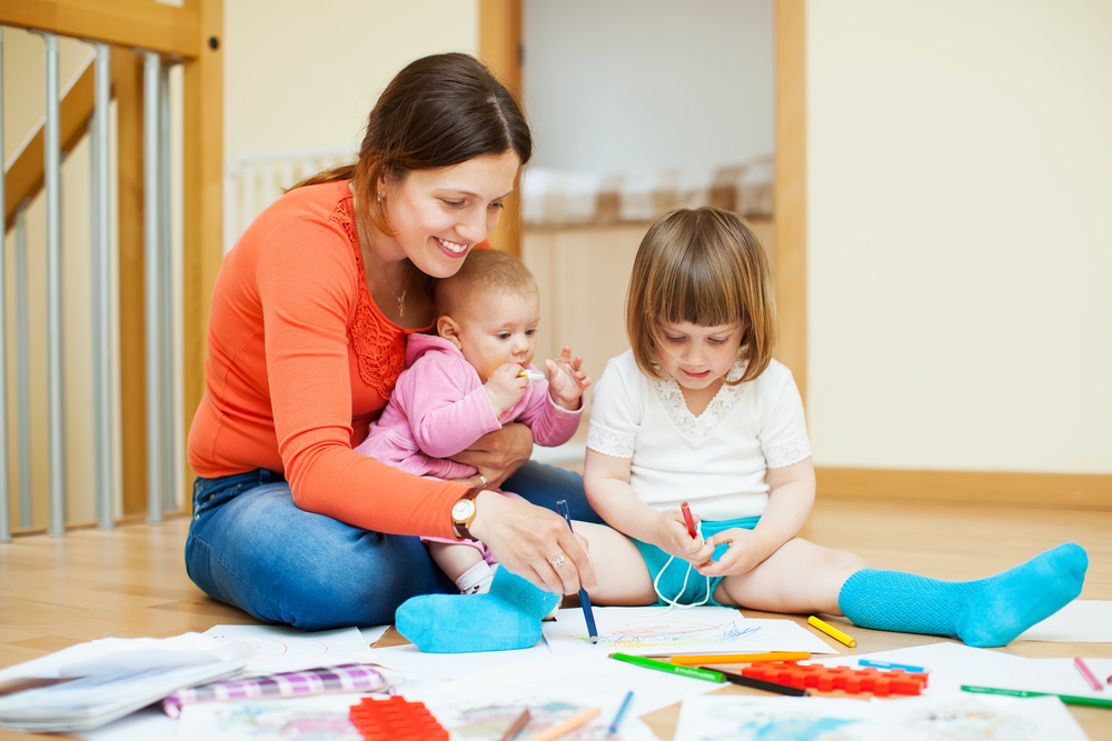 mother-with-her-kids-playing-indoors