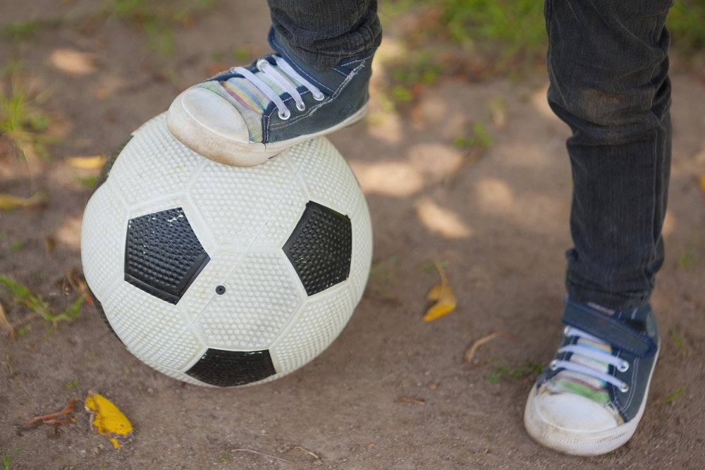 close-up-low-section-of-boy-with-one-leg-on-football-at-the-park