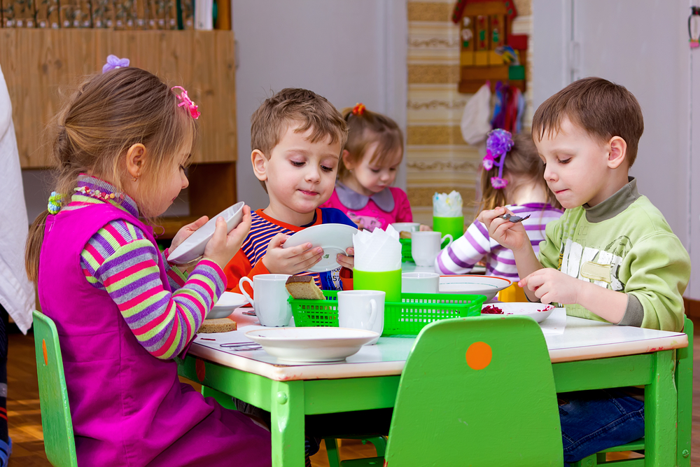 boys-and-girls-from-the-group-of-children-sitting-at-the-table-with-lunch-and-eat-appetizing