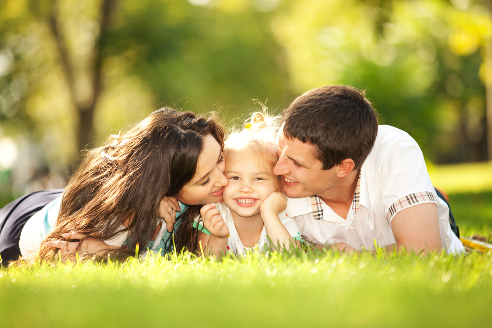 happy-mother-and-father-kissing-their-daughter-in-the-park
