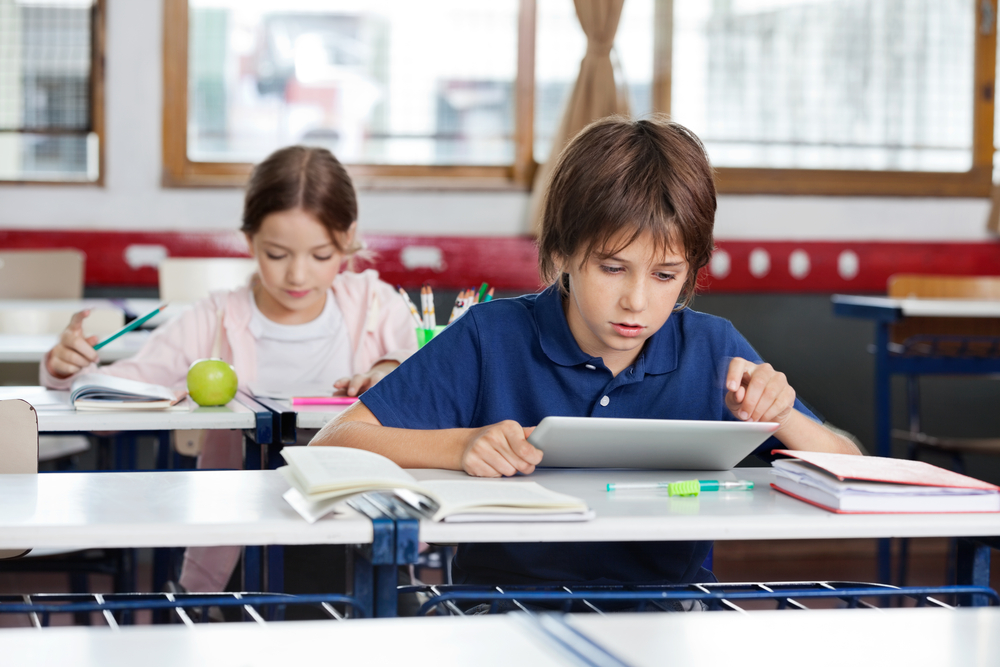 little-school-boy-using-digital-tablet-with-girl-studying-in-background-at-classroom