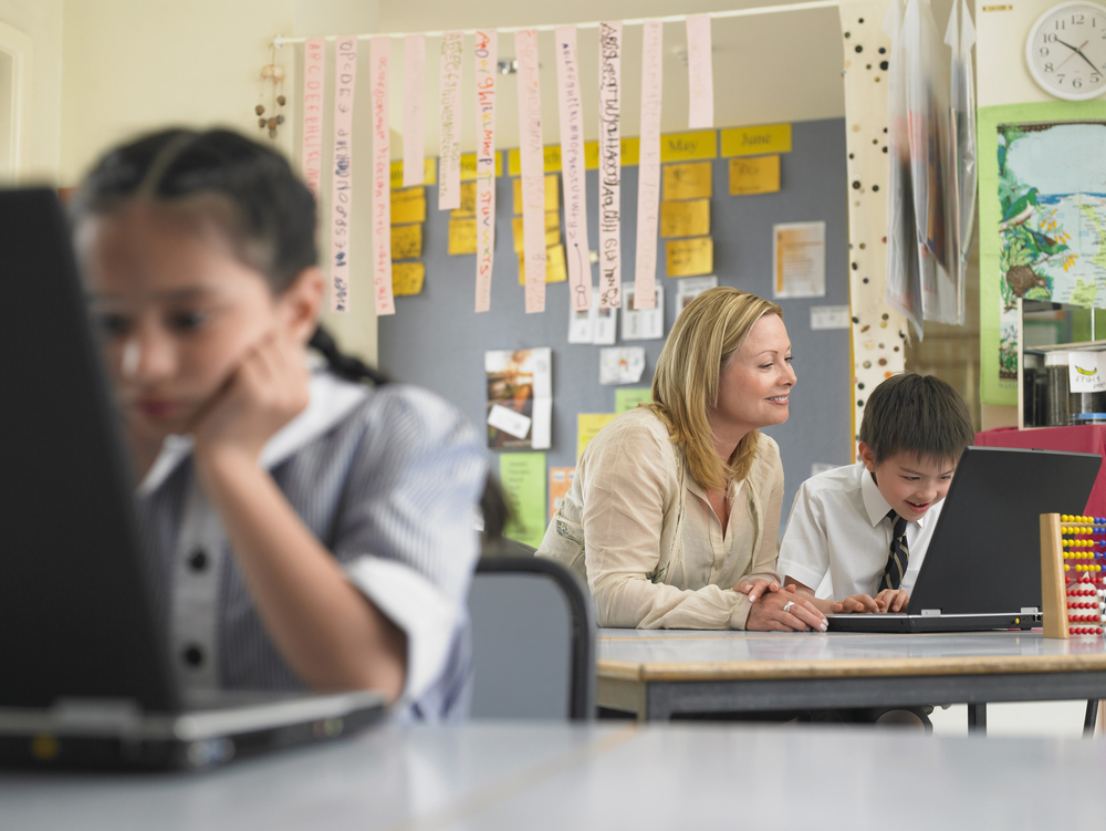 teacher-and-schoolboy-using-laptop-with-girl-in-foreground-at-classroom