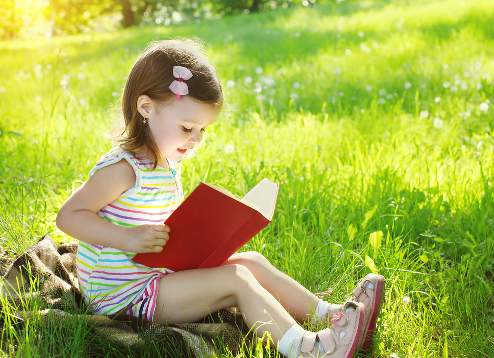 child-reading-a-book-on-the-grass-in-sunny-summer-day