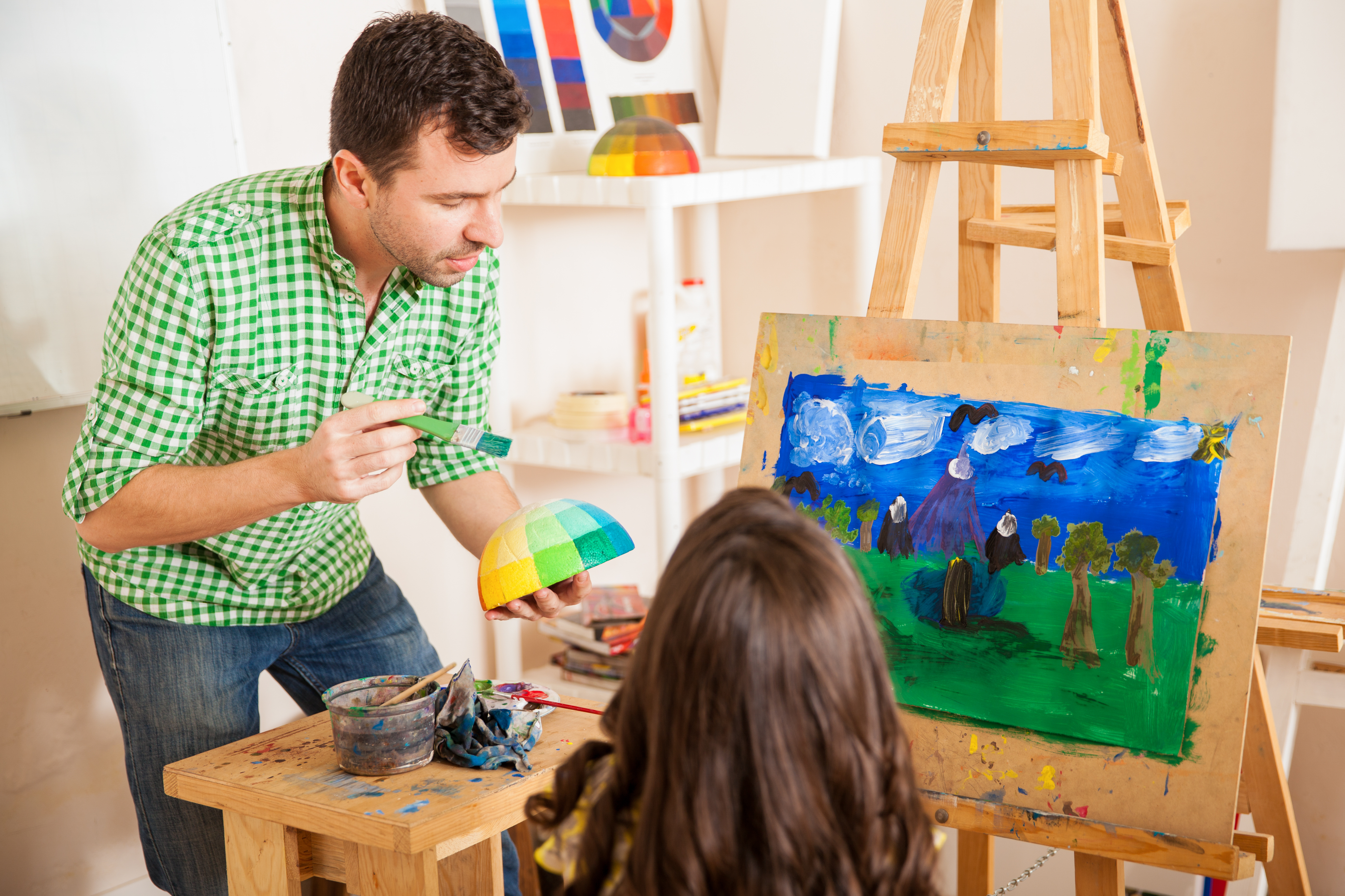 young-art-teacher-talking-about-colors-with-a-little-girl-during-class
