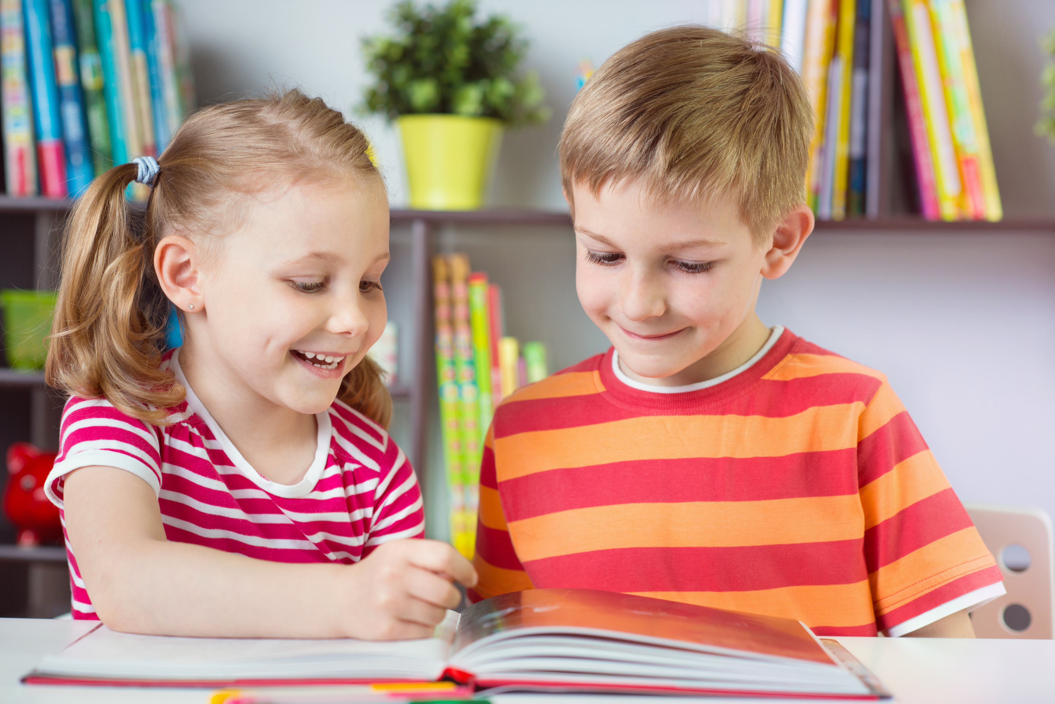 two-happy-siblings-reading-interesting-book