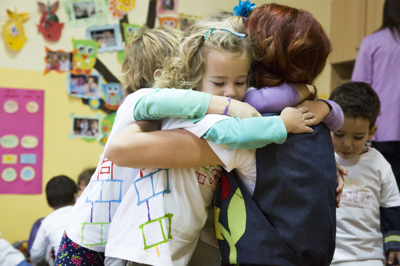 Vaspitačica u zagrljaju sa decom iz Školice života u Lepenici, opština Vladičin Han.