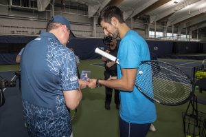 Prizeo lottery winner, Dave Wills gettiing a signed autograph from Novak Djokovic